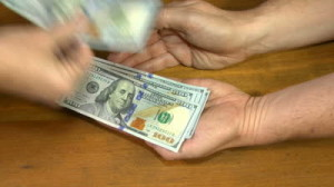 stock-footage-close-up-of-one-person-counting-us-dollar-bills-into-the-hands-of-another-waiting-person
